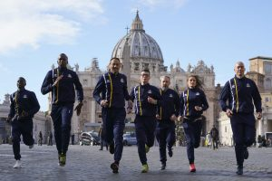 Athletes of the Athletic Vatican sports team run for the media in front of St. Peter's basilica, at the Vatican, Thursday, Jan. 10, 2019. The Vatican has launched an official track team. About 60 Holy See employees are the first accredited members of Vatican Athletics. They include Swiss Guards, priests, nuns, pharmacists and even a 62-year-old professor who works in the Vatican's Apostolic Library. (AP Photo/Andrew Medichini)